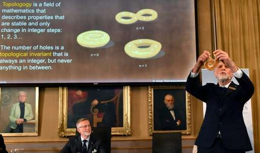 Thors Hans Hansson (R), member of the Nobel Committee for Physics, uses a pretzel to visualize his explanations during a press c