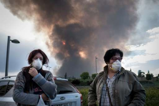 Two neighbours in Sesena, near Madrid wear masks as they wait for relatives to evacuate a residential area affected by toxic fum