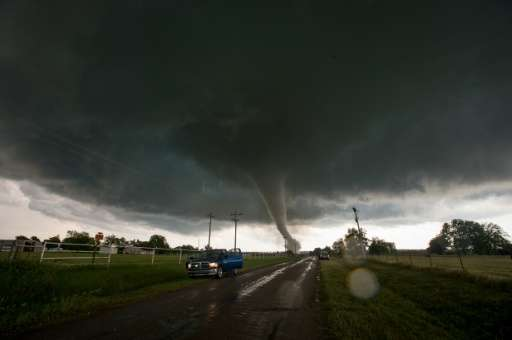 Vehicles stop on the side of a road as a tornado rips through a residential area south of Wynnewood, Oklahoma on May 9, 2016