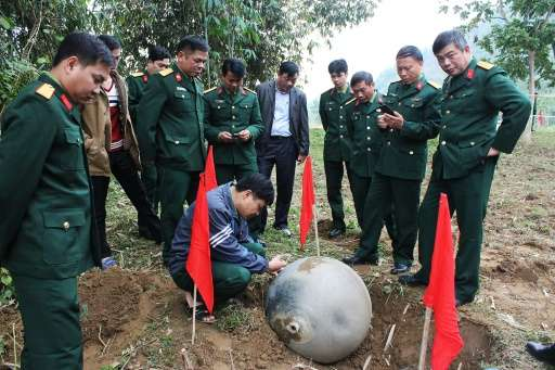 Vietnamese soldiers inspect a metal ball which landed in the northern province of Tuyen Quang