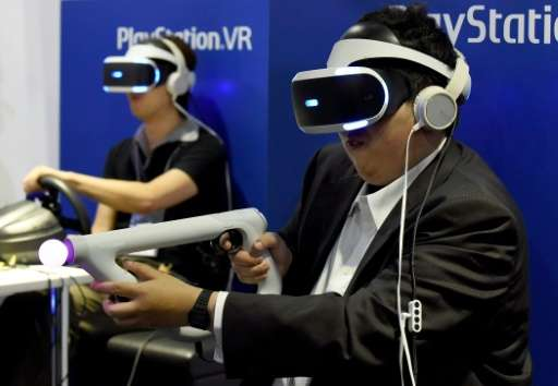 Visitors play a virtual reality game at Sony's booth during the Tokyo Game Show 2016, in Chiba, suburban Tokyo