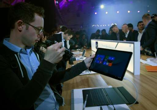 Visitors take pictures of a Matebook during Chinese company Huawei's presentation on the eve of the official opening of the Mobi