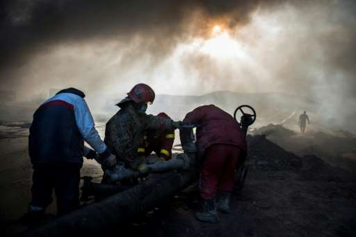 Workers tasked with putting out the fire in an oil well assemble a water pipeline in the town of Qayyarah, some 70 km south of M
