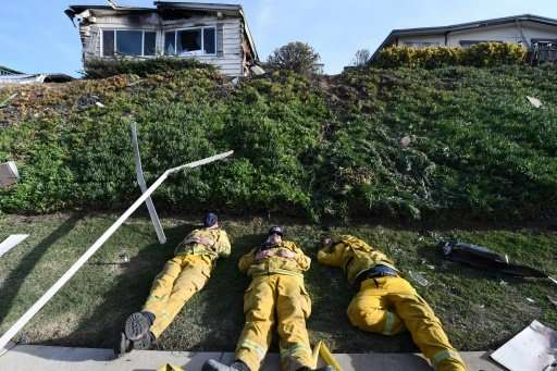 Exhausted firefighters have their first rest in over 20 hours since starting to fight the Lilac Fire, December 8, 2017, in Bonsa