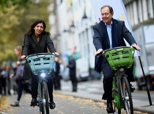 Paris Mayor Anne Hidalgo (L), who is on an crusade to clean up the city's air, aims to lure more Parisians into the saddle