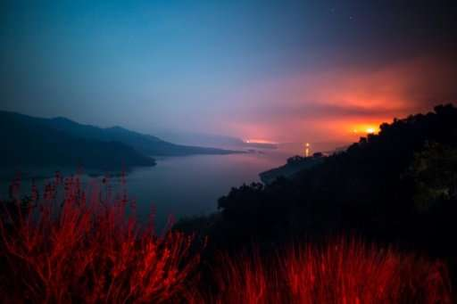 The Thomas Fire burns a hillside behind Lake Casitas in Ventura, California on December 8, 2017