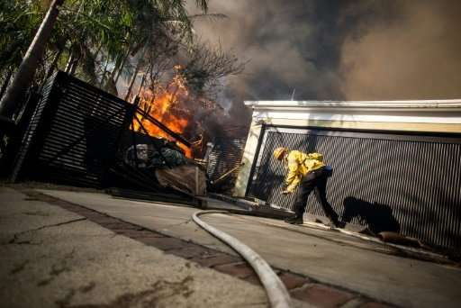Firefighters work to save burning houses in the Skirball Fire near Los Angeles
