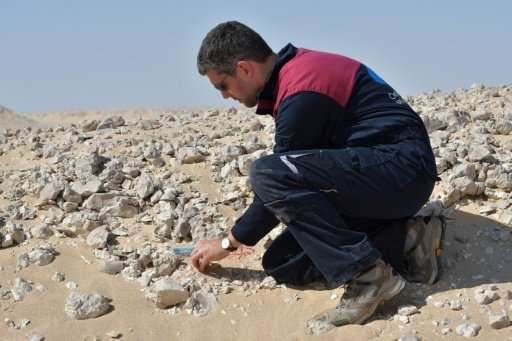 A member of the Austrian Space Forum inspects a site in Oman's Dhofar desert, near the southern Marmul outpost, on October 29, 2