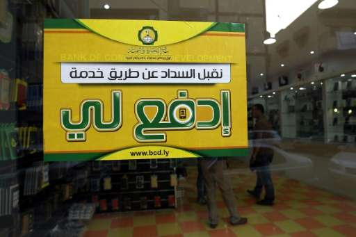 """A  picture taken on July 24, 2017 shows a poster of the """"Edfali"""" (Arabic for """"pay me"""") mobile phone app in a"""