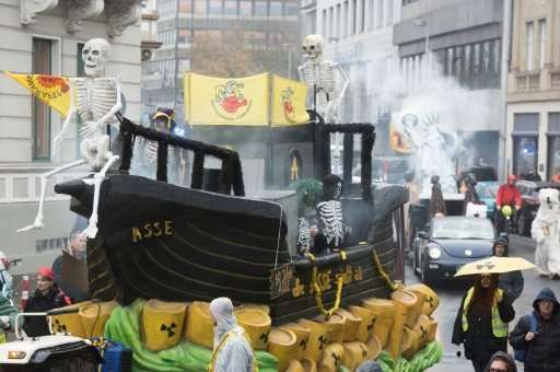 Demonstrators dressed as human skeletons stand on a ship-designed float swimming on symbolical nuclear waste during a protest of