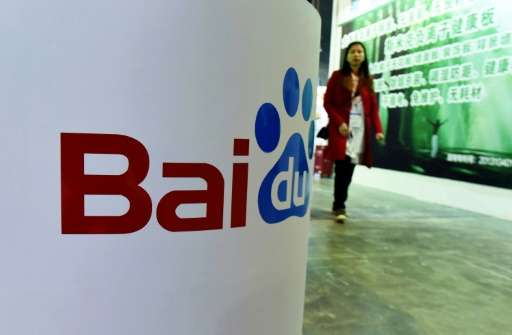 This photo taken on April 21, 2016 shows a woman walking past the Baidu booth at the China (ShangHai) International Technology F