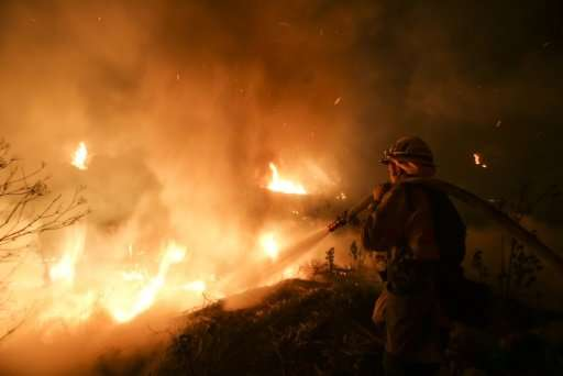 Firefighters battle flames on a hillside near homes in Santa Paula, California, as the Los Angeles region grapples with wind-whi