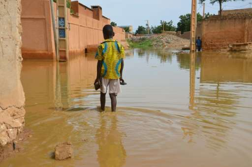 A child walks in muddy water in the Saga district of Niamey on September 11, 2017 as streets are flooded by the overflowing Nige