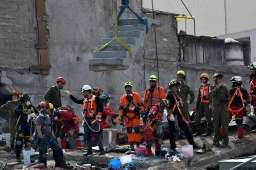 A crane removes concrete stairs as rescuers pause at the remains of a quake-stricken building at Colonia Roma in Mexico City
