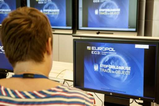A Europol police agent looks at the onscreen logo of a new website launched by Europol at the Europol headquarters in The Hague