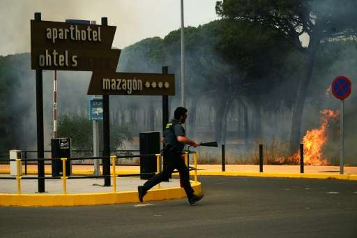 A Guardia Civil officer battling a wildfire near Mazagon in southwestern Spain, which has forced more than 2,000 people to evacu