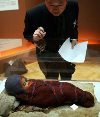 A journalist looks at a baby mummy which was unearthed at an ancient tomb in Chinese city of Qarqan. The Kyrgyzstan mummy ""