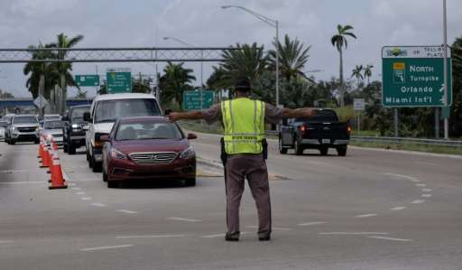 A law enforcement officer directs traffic at a checkpoint preventing residents of the Florida Keys from returning to their homes