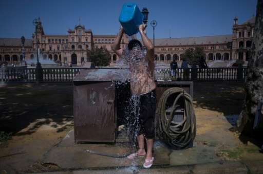 A man cools with a bucket of water next to Plaza de Espana in Seville during a heat wave, on July 13, 2017