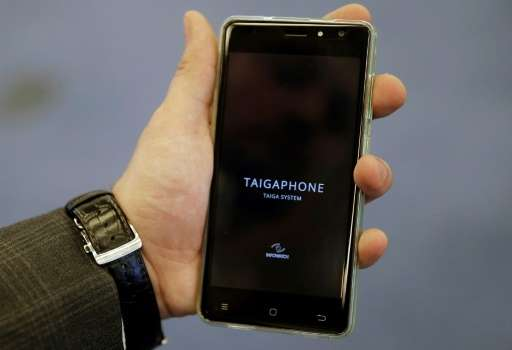A man holds a TaigaPhone, a brand new smartphone created by InfoWatch Group, during a presentation in Moscow on September 22, 20