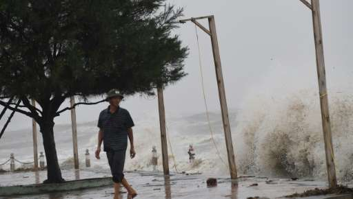A man looks at waves from a beach in Dien Chau district, central province of Nghe An as the typhoon Doksuri prepares to make a l