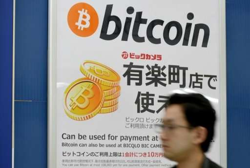 A man walking past a signboard in Tokyo informing customers that Bitcoin can be used for payment, as more and more major compani
