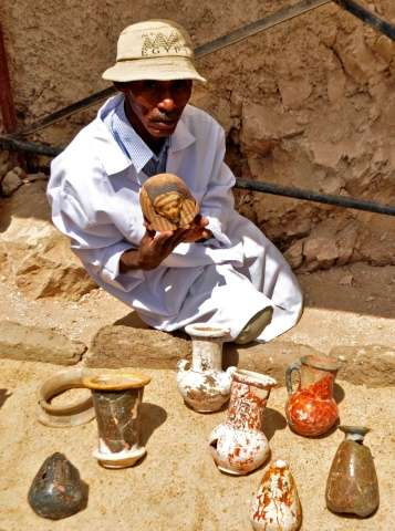 A member of an Egyptian archaeological team shows artifacts discovered in a 3,500-year-old tomb in the Draa Abul Nagaa necropoli