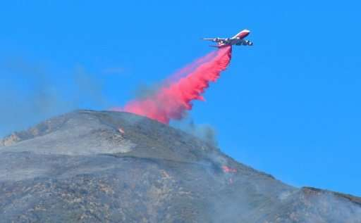 An aircraft drops retardant over  burning embers and small fires on top of a mountain in Fillmore, California on December 8, 201