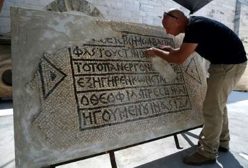 An archaeologist works on a 1,500-year-old section of floor mosaic bearing the name of Byzantinian Emperor Justinian, at the Roc