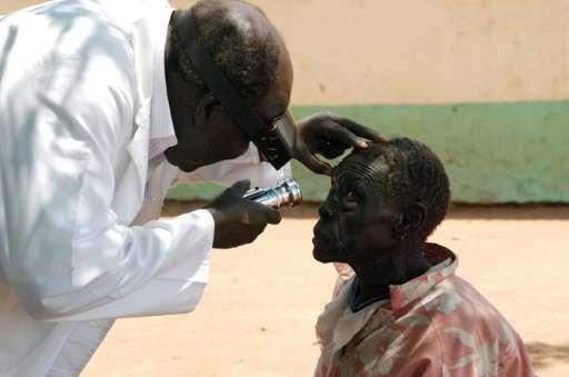 An eye specialist checks the eyes of an elderly patient in Juba