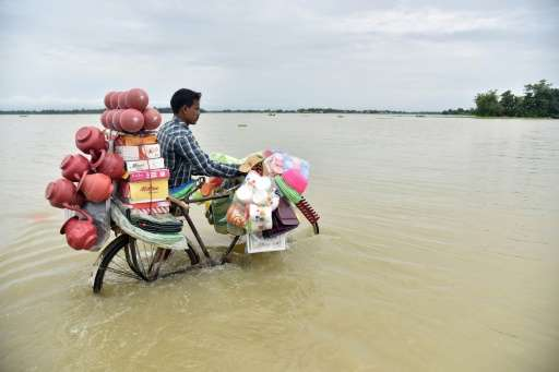 An Indian vendor pushes a bicycle carrying his wares through floodwaters in Balimukh Ashigarh village in Morigoan district, in I