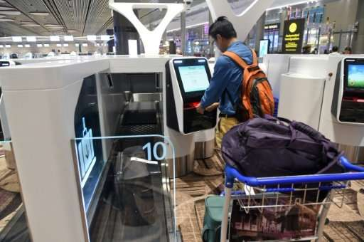 A passenger checks-in his luggage using an automated booth at the newly opened Changi International Airport's Terminal 4 in Sing