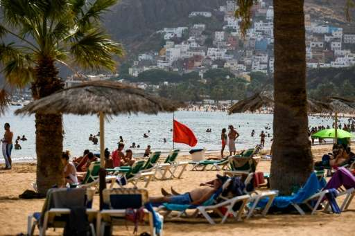 A red flag, informing bathers that swimming is not allowed, flies over Tenerife's Las Teresitas beach