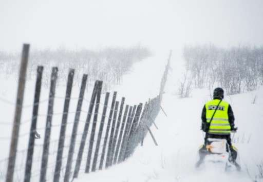 A reindeer police officer rides his snow scooter as he patrols in Finnmark county in northeastern Norway