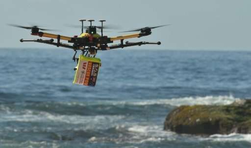 A shark-spotting drone with safety flotation device attached flies over Bilgola beach, Sydney