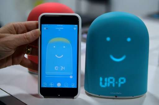 A smartphone is placed next to Remi—a smart alarm clock for kids which offers a night tracke and a storyteller—on display at the