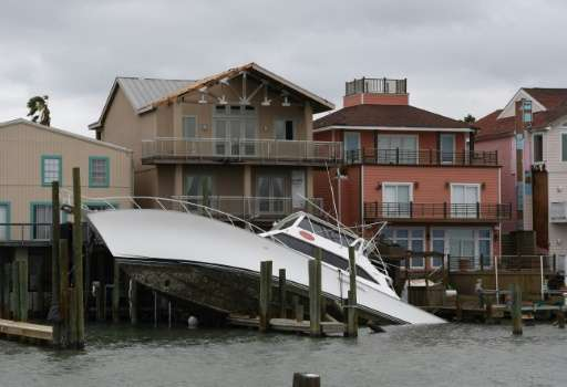 A sunken boat lies submerged in front of houses after Hurricane Harvey hit Port Aransas, Texas