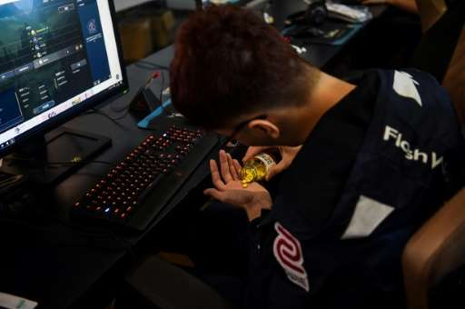 A Taiwanese gamer from the eSports team Flash Wolves takes Vitamin B pills during training for the League of Legends World Champ