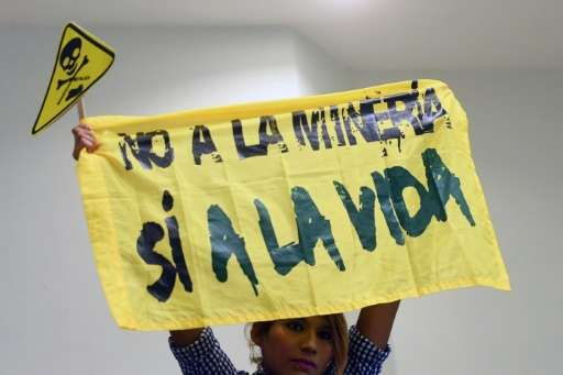 """A woman holds a banner reading """"No to mining. Yes to life"""" during a protest against mining at the Legislative Assembly"""
