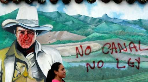 """A woman is seen in front of a wall with a graffiti reading """"No canal, no law"""" during a protest against the constructio"""