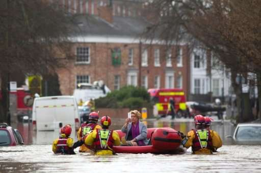 A woman takes a photograph as she is transported to safety by members of the emergency services, after homes were affected by fl