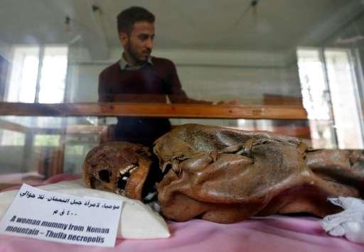 A Yemeni student looks at a millennia-old mummy on display at Sanaa University
