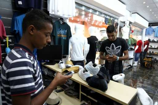 A young Libyan uses a mobile phone app to pay at a Benghazi store that accepts electronic payment systems