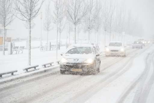 Cars drive slowly along a snow-covered road in Rotterdam during heavy snowfall.