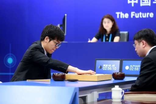 China's 19-year-old Go player Ke Jie (L) makes a move during the first match against Google's artificial intelligence programme