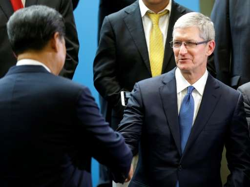 Chinese President Xi Jinping, left, shakes hands with Apple CEO Tim Cook, right, during a gathering of CEOs and other executives