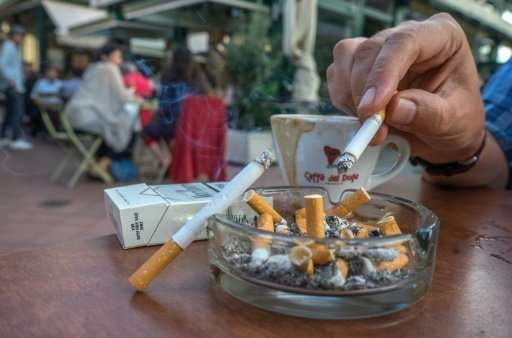 Clients of a coffee shop enjoy cigarettes with their drinks at  Vienna's most famous market, the Naschmarkt
