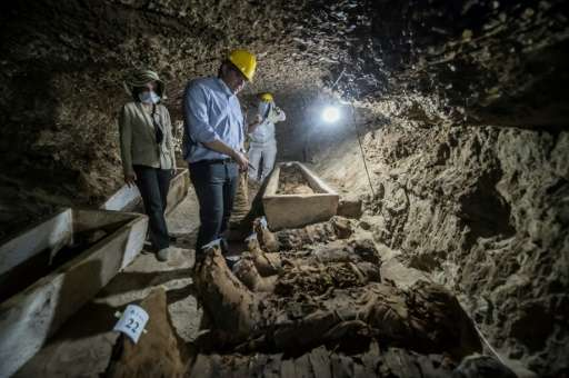 Egyptian Antiquities Minister Khaled el-Enany (C) speaks to media on May 13, 2017, in front of mummies discovered in catacombs i