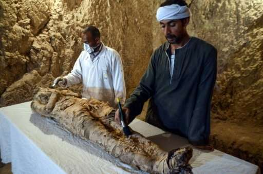 Egyptian archaeological technicians restore a mummy wrapped in linen, found at Draa Abul Naga necropolis on the west bank of the
