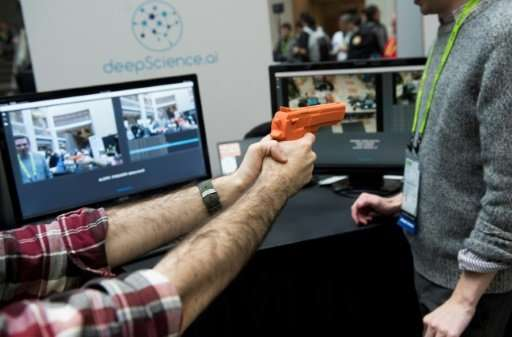 Elliot Hirsch of Deep Science holds a fake gun as he demonstrates the company's security system to automatically detect firearms